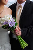 Wedding - focus on couple, holding hands together with bouquet of flowers — Stock Photo