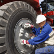 Mechanic and truck tire works — Stock Photo