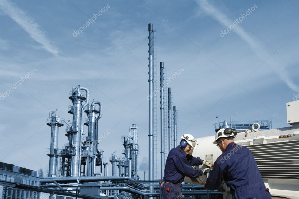 Two workers, engineers, with large oil and gas industry in background  Stock Photo #6421086