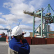 Stock Photo: Dock worker directing container crane