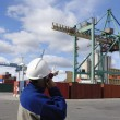 Dock worker directing container crane — Stock Photo
