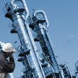 Worker with oil and fuel towers - Stock Photo