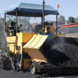 Asphalt paving and worker - Stock Photo