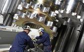 Engineers and steel machinery — Stock Photo