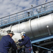 Oil workers and fuel tanks — Stock Photo