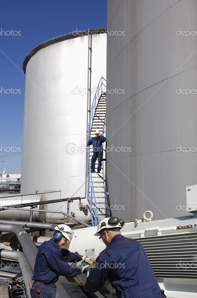Oil and gas worker talking in phone, standing on the stairs of large fuel tower, engineers and machinery in foreground — Stock Photo #6656487