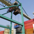 Stock Photo: Container crane hoisting containers