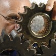 Engineer examining gear wheels - Zdjęcie stockowe