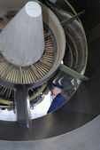 Airline captain inspecting jet-engine — Stock Photo