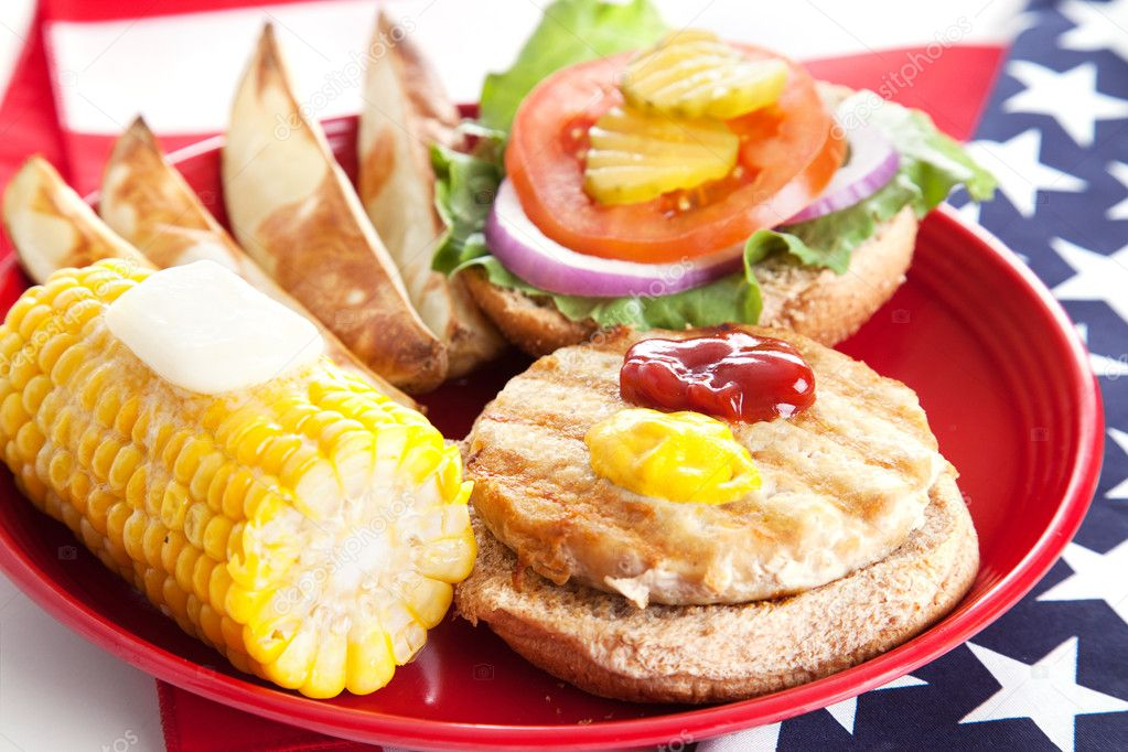 Delicious low-fat turkey burger on whole grain bun with baked potato wedges and corn.  Celebrating Fourth of July by eating healthy.   — Stock Photo #6411441