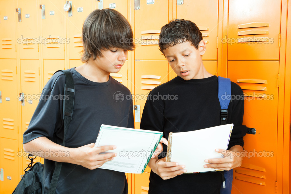Teenage boys by lockers, comparing answers in their homework workbooks.   — Stock Photo #6411447