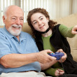 Teen Helps Grandpa with Video Game - Stock Photo