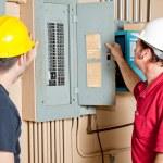 Repairmen Examine Electrical Panel — Stock Photo