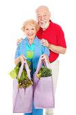 Senioren en herbruikbare shopping tassen — Stockfoto