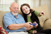 Teen Helps Grandpa with Video Game — Stock Photo
