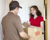 Young Woman Signs for Delivery — Stock Photo