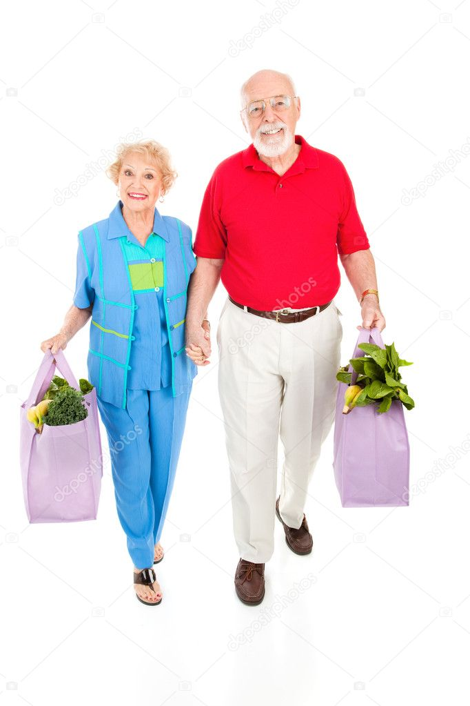Environmentally aware senior couple bringing home groceries in reusable bags.  Isolated on white. — Stock Photo #6511407