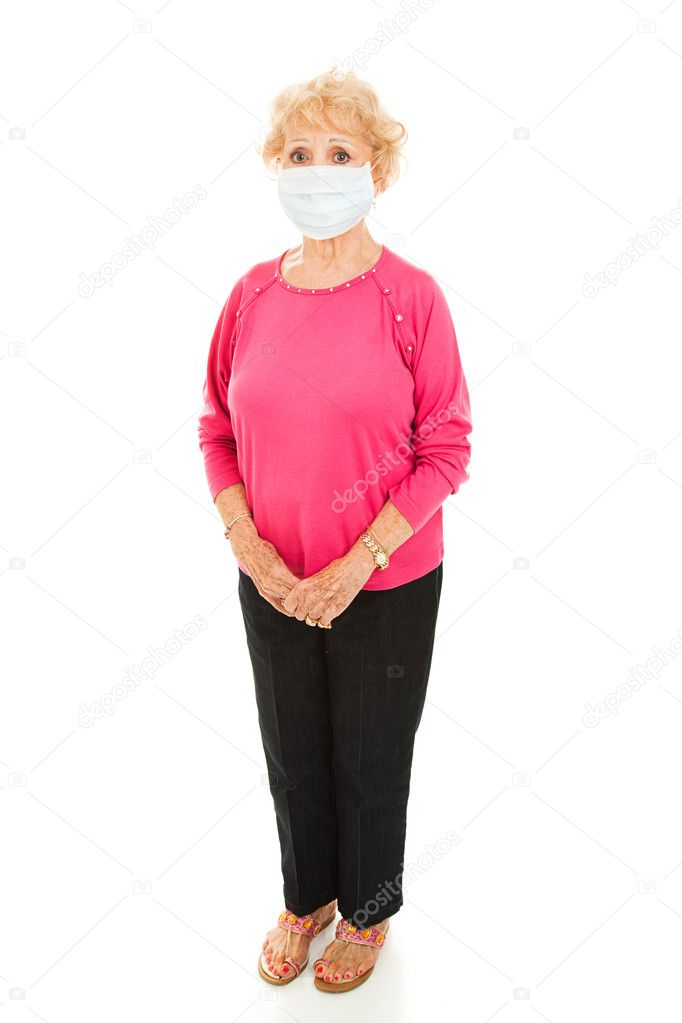 Full body isolated view of a senior woman wearing a face mask to protect against an epidemic.    Stock Photo #6511808