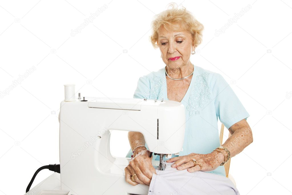 Senior woman making curtains on a sewing machine.  Isolated on white. — Stock Photo #6511889