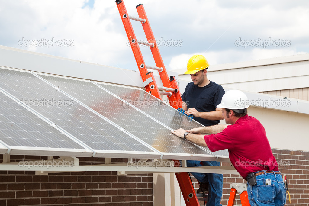 Workers install energy efficient solar panels on the roof of a building.   — Stock Photo #6516765