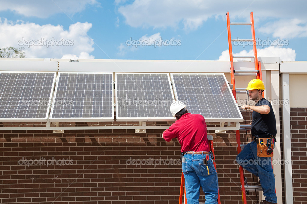 Workers installing solar panels on the side of a building.  Wide angle view with room for text. — Stock Photo #6516779