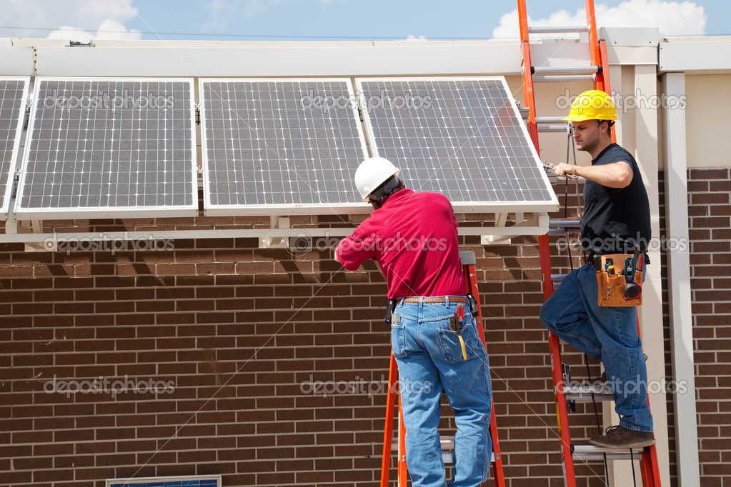 Two electricians installing solar panels on a building.    Stock Photo #6516788