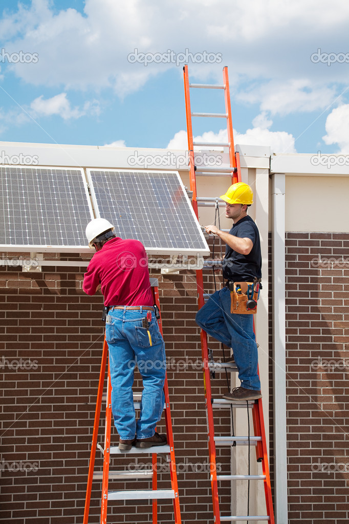 Two workers installing solar panels on the side of a building.  Vertical with room for text.    Stock Photo #6516805