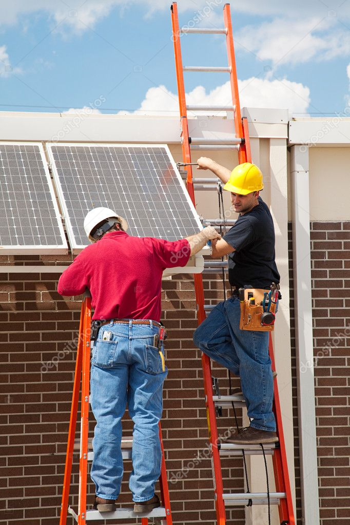 Construction electricians installing solar panels on the side of a building. — Stock Photo #6516818