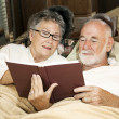 Senior Couple Reading in Bed - Stock Photo
