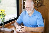 Senior Man Shuffles Cards — Stock Photo