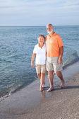 Seniors Stroll on Beach — Stock Photo