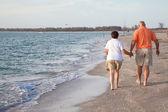 Senioren wandelen op het strand — Stockfoto