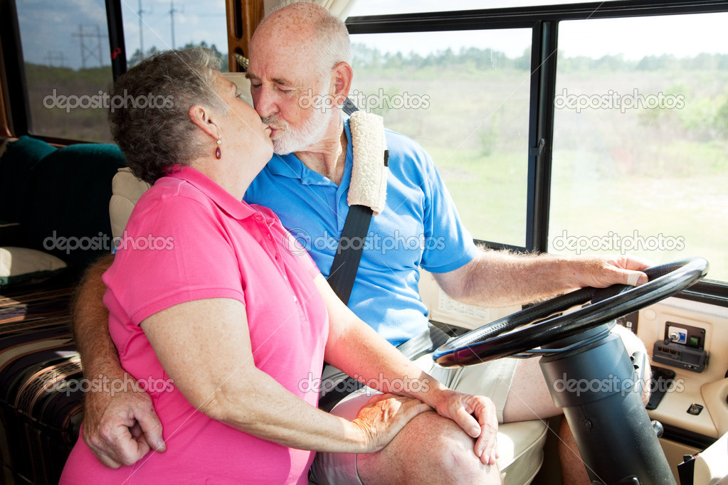 Vacationing senior couple kissing while he is driving their motor home.   — Stock Photo #6555249