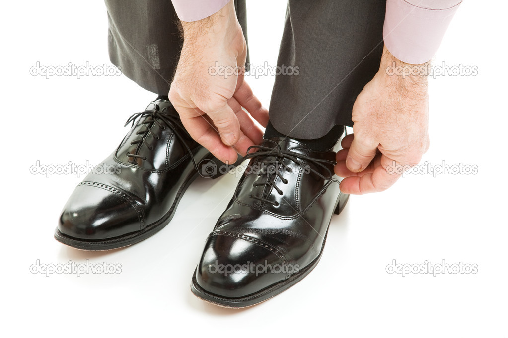 Man ties his shiney new black leather business shoes.  Isolated on white. — Stock Photo #6555745