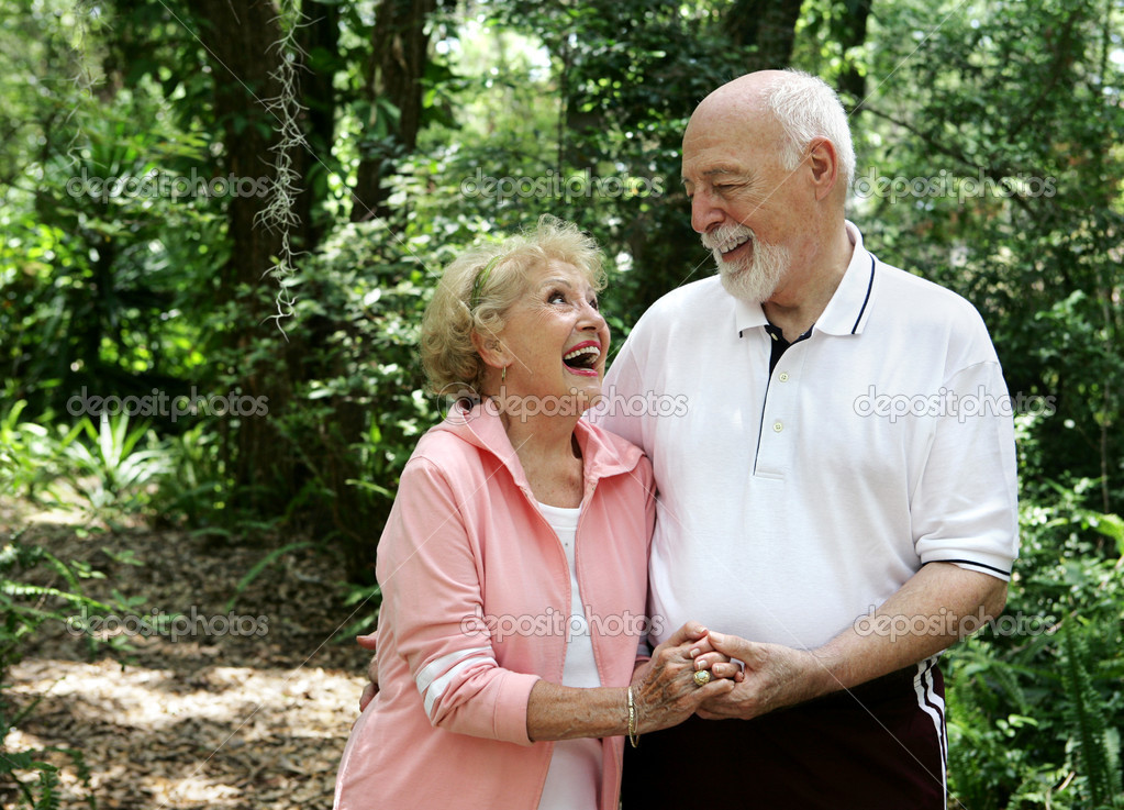 A happy, active senior couple laughing together on a walk through the park.  She's wearing a hearing aid.  Plenty of copyspace.    Stock Photo #6574616