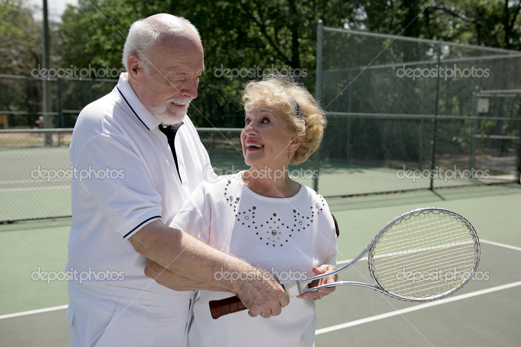 A senior couple playing tennis together.  He's showing her how to grip her racquet.   — Stock Photo #6574625