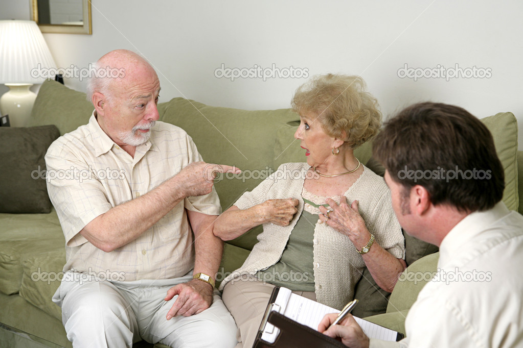 A senior couple seeking marriage counseling.  He's pointing at her and she's looking surprised.  Focus on husband. — Stock Photo #6596561