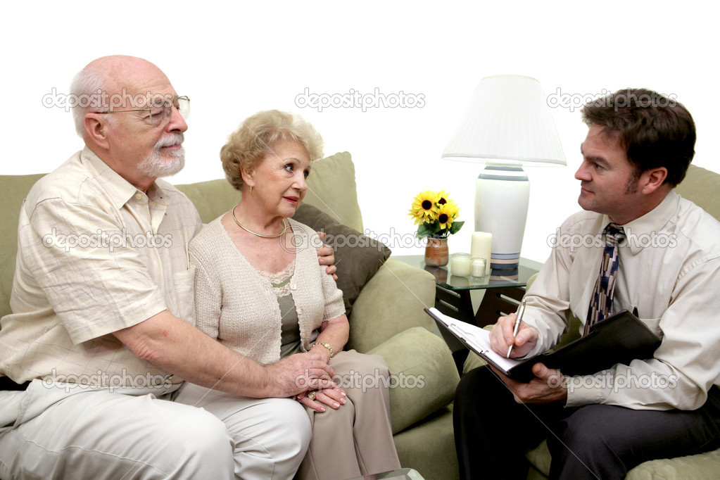 A senior couple speaking with a marriage counselor.  Could also be a salesman in their home.  Isolated on white with focus on couple. — Stock Photo #6596562