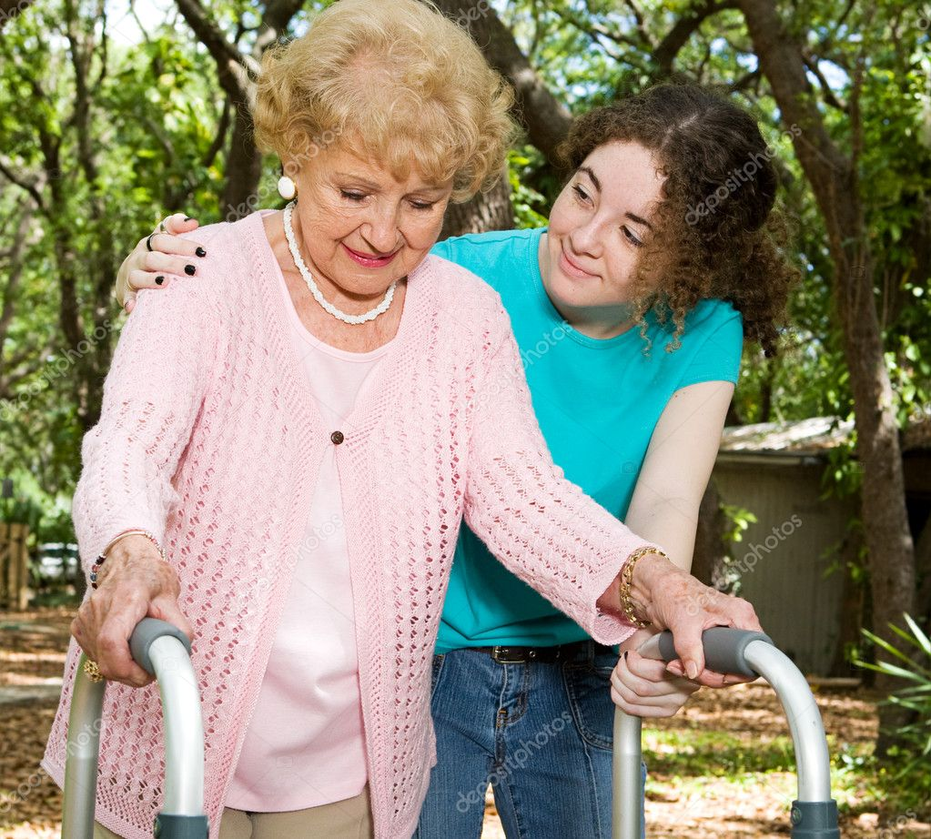 Teen girl helping a senior lady with a walker.   — Stock Photo #6596819