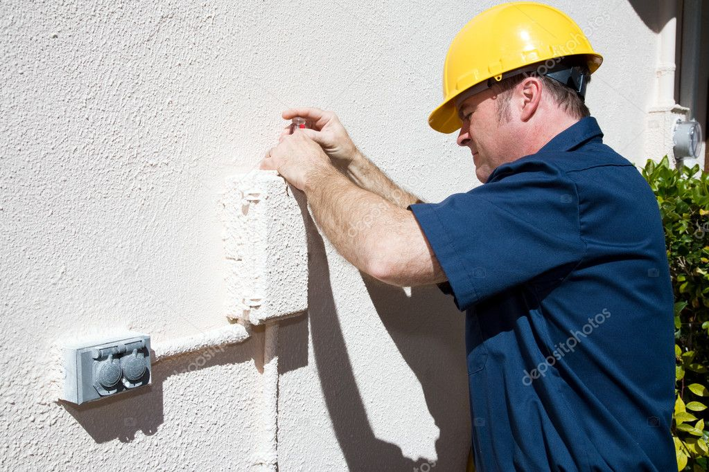 Repairman opening an outdoor box that has been painted shut.   — Stock Photo #6596907