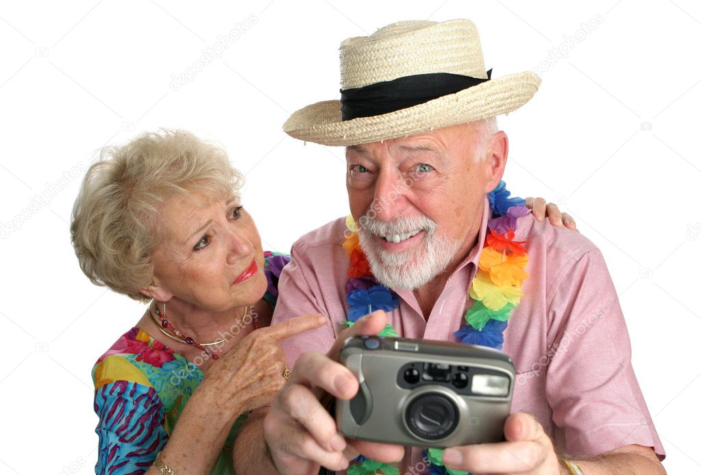 A senior man with a camera taking pictures of pretty girls on the beach while his wife gets mad at him. — Stock Photo #6628544