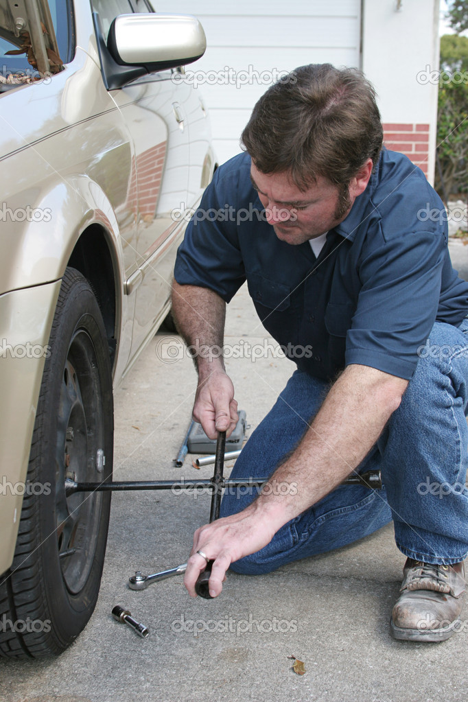 A mechanic changing a tire. — Stock Photo #6628635