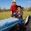Mature Farm Couple on Tractor - Stock Photo
