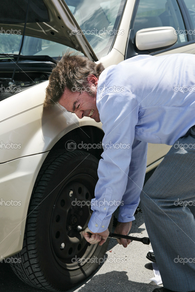 A businessman with a flat tire on the road strains to uncrew the lug nuts.   — Stock Photo #6650636