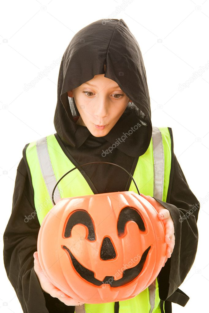 Adorable little boy in his halloween costume and a reflective safety vest, eying the candy in his pumpkin bucket.  Isolated on white.   — Stock Photo #6652133