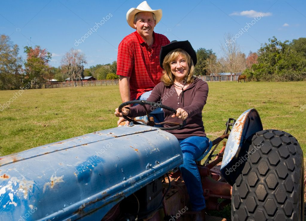 Beautiful mature couple riding a tractor on their farm.