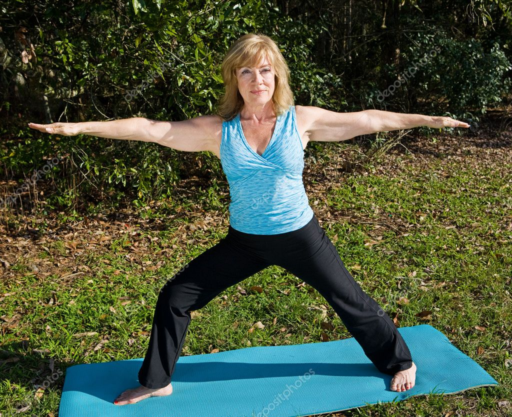 Fit beautiful sixty year old woman doing the warrior pose in yoga in a natural setting.   — Stock Photo #6652406