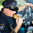 Stock Photo: Police Officer Eating Donut