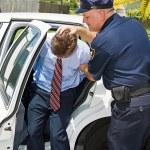 Shoved in Police Car — Stock Photo