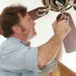 Electrician Installing Ceiling Fan - Stock Photo